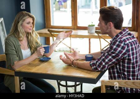 Jeune couple de parler tout en ayant à table de café en café Banque D'Images