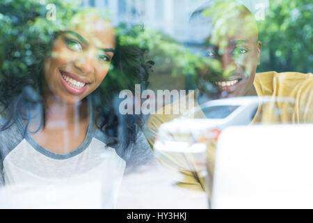 Portrait of happy young couple in coffee house vu à travers la vitre Banque D'Images
