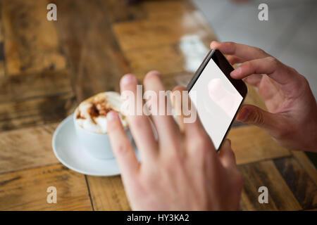 Close-up of man mains photographier par café smart phone in cafe Banque D'Images