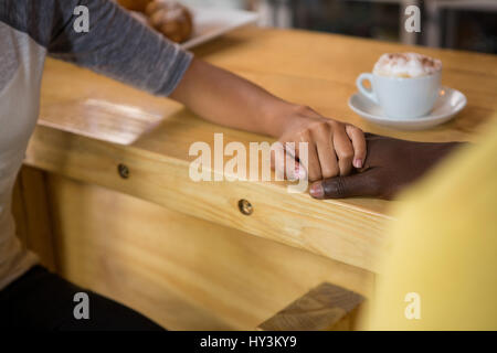 Portrait of multi ethnic couple holding hands in coffee house Banque D'Images