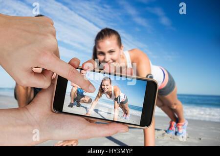 Les mains de toucher smart phone contre portrait de couple exercising on sand Banque D'Images