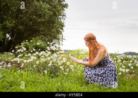 La Finlande, Pirkanmaa, Tampere, femme photographiant fleurs dans la prairie Banque D'Images