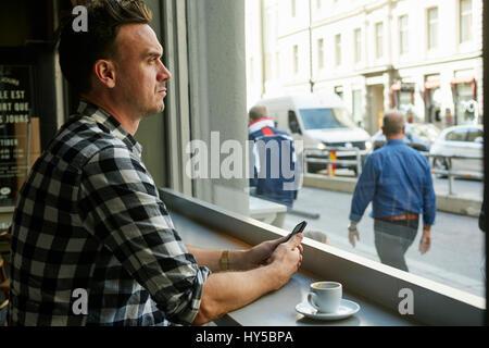La Suède, man holding cellulaire et à la recherche à travers la vitre en cafe Banque D'Images