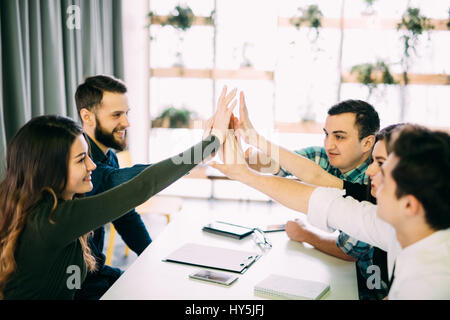 Haut-cinq collègues donnant dans la salle de réunion au bureau créatif prix Banque D'Images