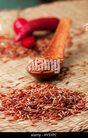 Riz rouge dans une cuillère en bois, le riz et le poivron rouge sur un fond de paille Banque D'Images