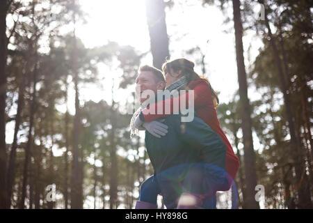Un homme donne sa partenaire féminine un piggy back sur une promenade n les bois Banque D'Images