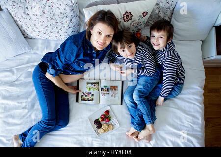 Belle maman et deux enfants, des garçons, allongé sur le lit, de manger des fraises et des biscuits, looking at Banque D'Images