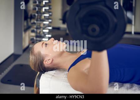 Close-up portrait of young blonde woman in blue page faire de l'exercice développé couché avec bar-bell in gym Banque D'Images