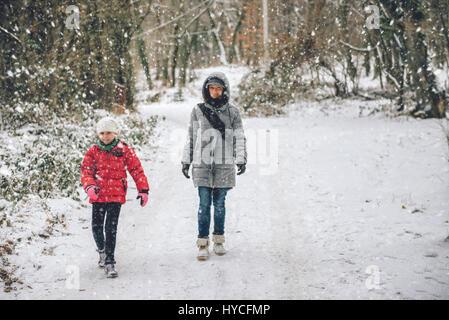 Mère fille avec randonnées en forêt d'hiver blanc Banque D'Images