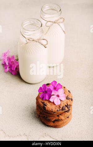Pile de cookies aux pépites de chocolat avec deux bouteilles de lait et des fleurs roses sur le tableau gris rustique Banque D'Images