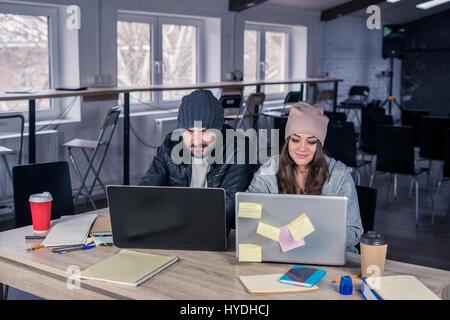 Couple d'étudiants qui étudient à l'université hipster avec des ordinateurs portables en salle de conférences. L'environnement Banque D'Images