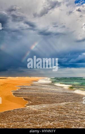 Rainbow dans des rayons de lumière pendant une tempête de pluie au-dessus de plage de sable et le surf, les vagues de l'océan Pacifique dans la région de Stockton Beach, NSW, Australie.
