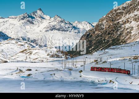 Red train Bernina Express passant Lago Bianco dans un paysage de montagne d'hiver, Grisons, Suisse