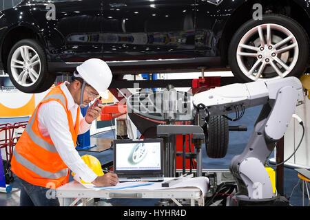 Ingénieur automobile avec l'aide d'inspecter robotique, l'industrie automobile moderne concept 4.0 Banque D'Images