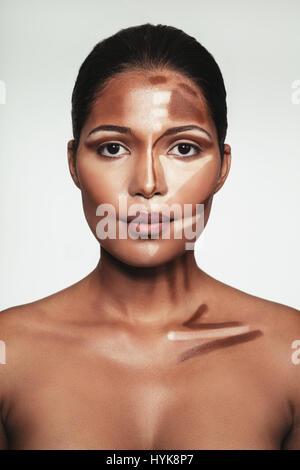 Close up portrait of young woman avec contour et mettez un miroir sur le visage contre l'arrière-plan blanc. Visage Banque D'Images