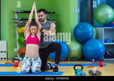 Young woman working out avec un entraîneur personnel dans la salle de sport. Banque D'Images