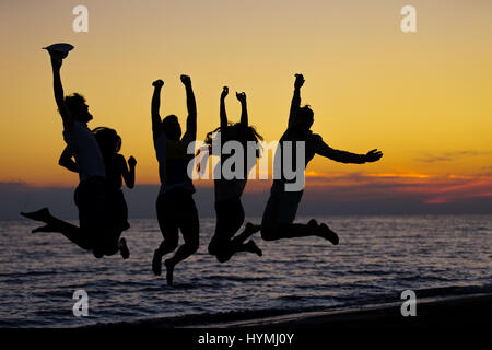 Silhouette d'amis sautant sur plage, pendant l'heure du coucher du soleil Banque D'Images
