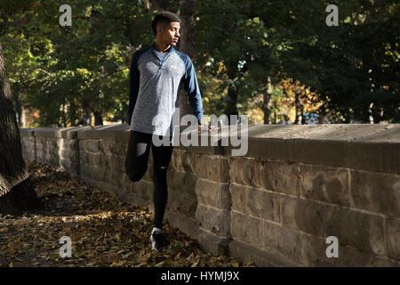 Un portrait d'un jeune homme qui s'étend alors qu'il se prépare à faire de l'exercice. Tourné au cours de l'automne Banque D'Images