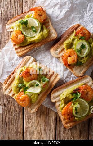 Délicieux toasts de guacamole, crevettes et lime gros plan sur la table. Vue verticale d'en haut Banque D'Images