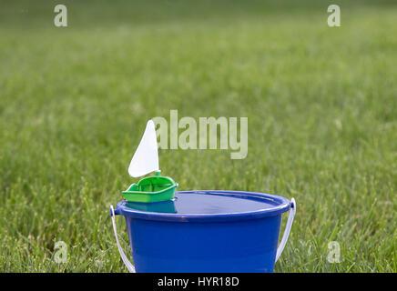 Un petit voilier jouet en plastique flottant dans un seau d'eau. Banque D'Images