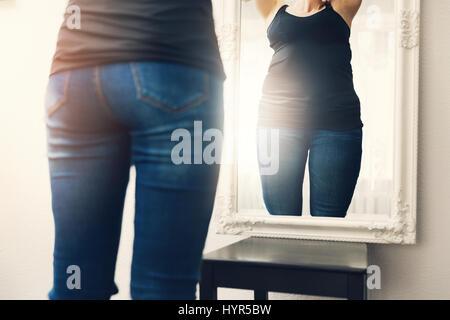 L'anorexie concept - femme regarde son reflet dans le miroir de la graisse Banque D'Images