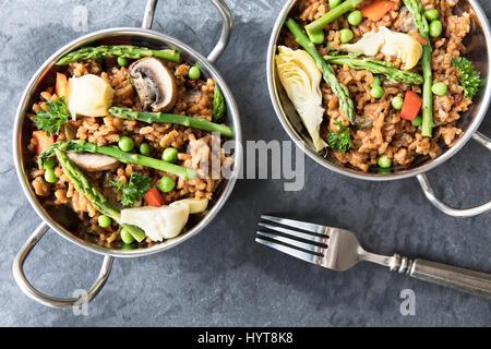 Deux bols de paella vegan aux asperges, champignons et d'artichauts - mise à plat. Banque D'Images