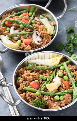 Deux bols de paella vegan aux asperges, champignons et d'artichauts. Banque D'Images