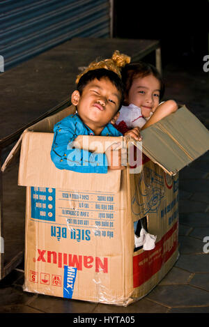 Portrait vertical d'enfants qui jouent à l'intérieur d'une boîte en carton au Cambodge. Banque D'Images
