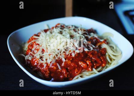 Délicieux spaghetti bolognese avec olives et fromage mozzarella sur fond sombre. Banque D'Images