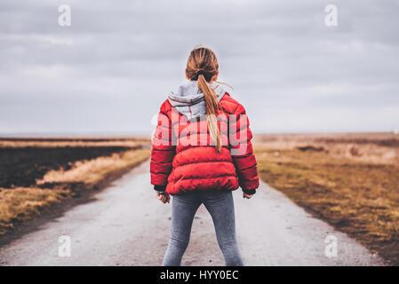 Girl wearing red jacket debout seul sur la route et à la recherche à distance Banque D'Images