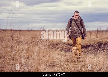 Randonneur et petite promenade de chien jaune dans l'herbage dans un jour nuageux Banque D'Images