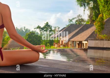 Bon matin avec yoga méditation de lever du soleil. Woman in bikini active la pratique sur la piscine villa pour Banque D'Images