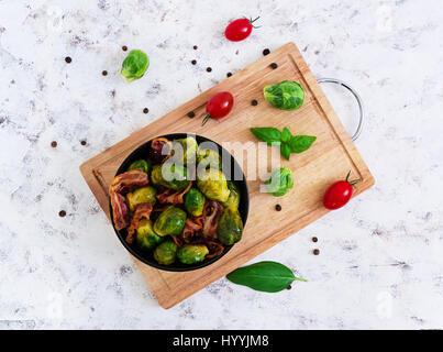 Choux de Bruxelles aux lardons grillés sur fond blanc. Vue d'en haut