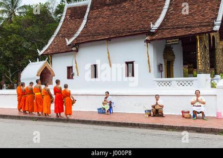 République démocratique populaire du Laos, Laos, Luang Prabang - 22 juin 2014: femme prie après l'aumône aux moines Banque D'Images