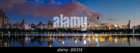 Vue panoramique sur le réservoir de Central Park et les gratte-ciel de Midtown allumé au crépuscule en été. Manhattan, Banque D'Images
