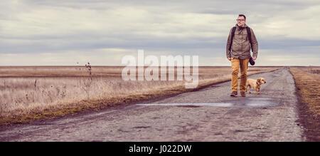 Randonneur et promener le chien sur une route sur un jour nuageux Banque D'Images