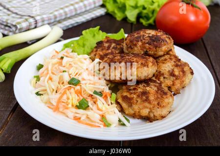 Escalopes juteuses et une salade avec des légumes frais: le chou, les carottes, les verts sur une plaque blanche. Banque D'Images