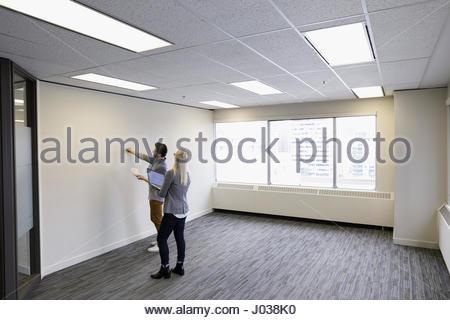 Les gens d'affaires sur des échantillons de peinture de visualisation en mur nouveau bureau vide Banque D'Images