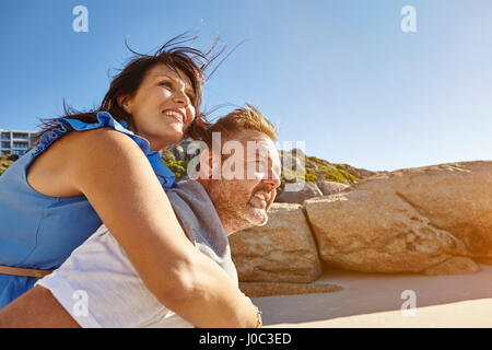 Man carrying woman on Beach, Cape Town, Afrique du Sud Banque D'Images