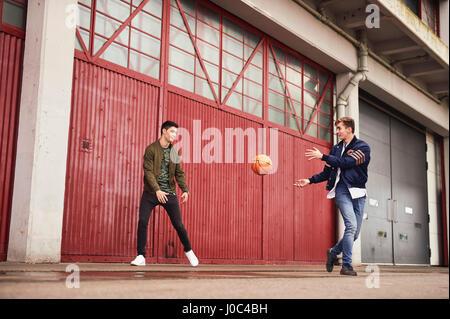 Deux jeunes hommes jouant au basket-ball en zone urbaine, Bristol, UK Banque D'Images