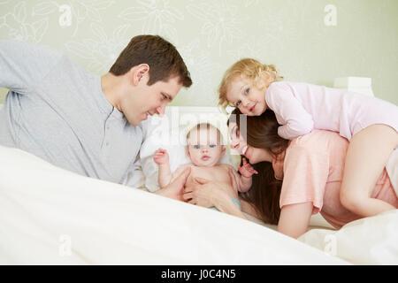 Femme enfant et bébé sœur jouant dans le lit des parents