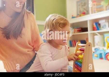 Mid adult woman and toddler fille compte sur abacus dans Jeux pour enfants Banque D'Images