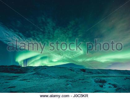 Aurora Borealis swirling vert pâle sur le paysage couvert de neige, le lac Kleifarvatn, Islande Banque D'Images