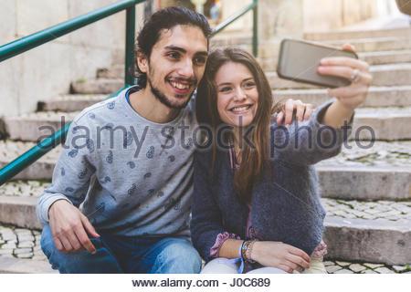 Jeune couple, assis sur les marches, en tenant avec selfies smartphone, Lisbonne, Portugal Banque D'Images