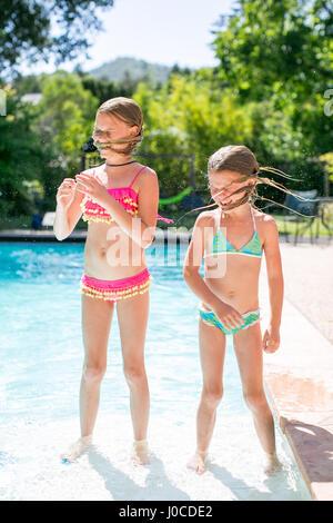 Deux sœurs secouant les cheveux mouillés par piscine extérieure Banque D'Images