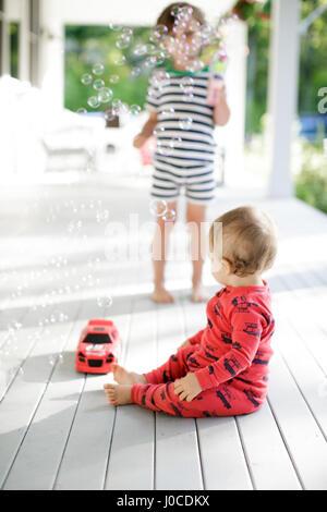 Tout-petit homme assis sur le porche à regarder boy blowing bubbles Banque D'Images