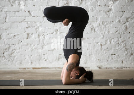 Jeune femme séduisante yogi dans wavecrest pose, zone loft blanc Banque D'Images