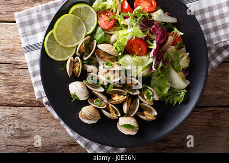 Palourdes fines avec de la chaux et de la salade de légumes frais sur une plaque. Vue du dessus horizontale Banque D'Images