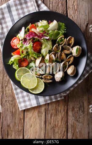 Palourdes fraîches avec de la chaux et des verts et salade printannière close-up sur une assiette. Vue verticale Banque D'Images