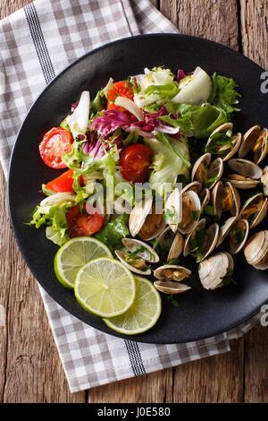 Palourdes fines avec de la chaux et de la salade de légumes frais sur une plaque. Vue verticale d'en haut Banque D'Images